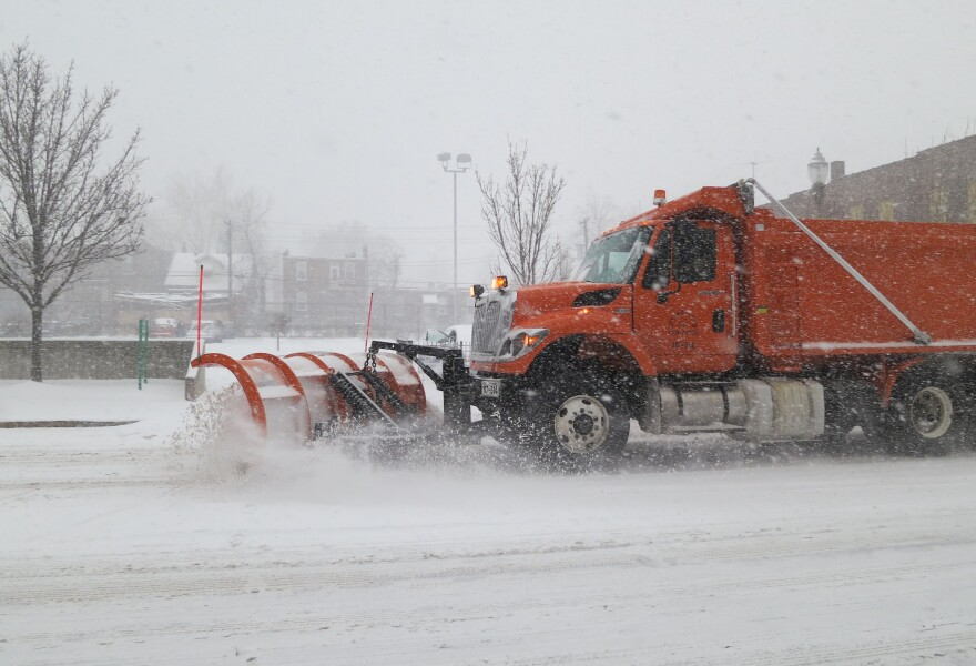 An orange truck pushes a plow on a road in St. Louis during a snow storm.