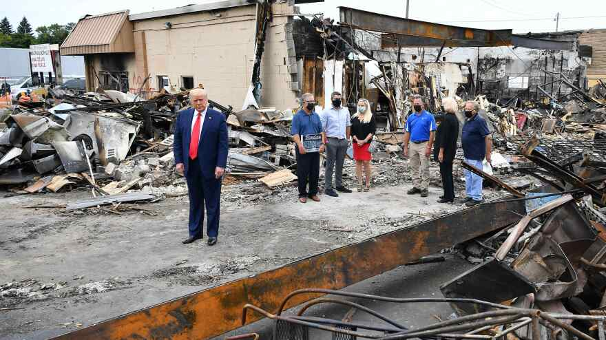 President Trump tours an area affected by civil unrest in Kenosha, Wis., on Tuesday. While there, he attacked Democratic leaders in other nearby big cities, saying they aren't doing enough on crime.