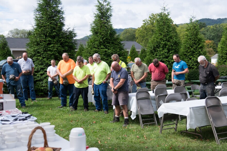White Sulphur Springs workers bow their heads in prayer before a City Hall-sponsored picnic.