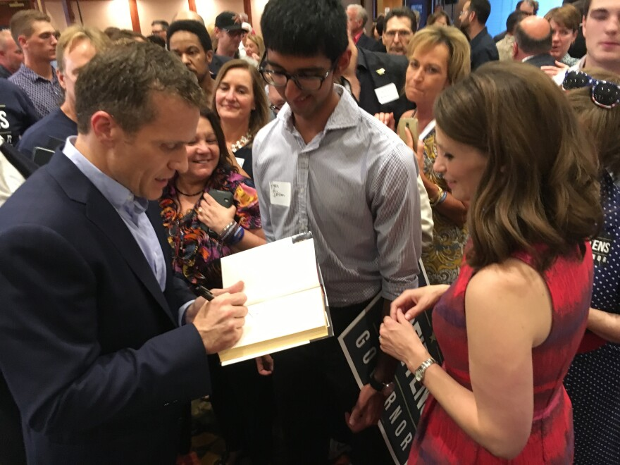 GOP gubernatorial nominee Eric Greitens, left, signs one of his books for one of his supporters. Greitens defeated three other Republicans on Tuesday.