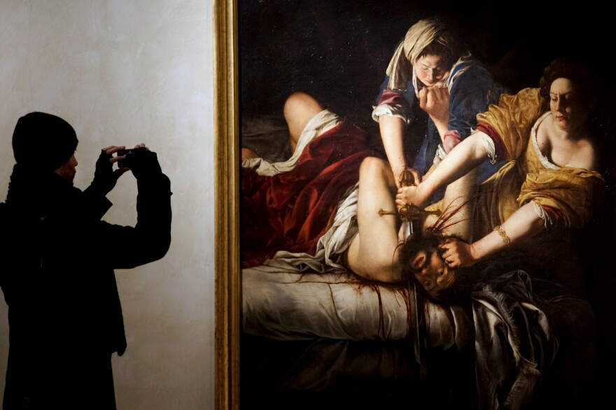 "A visitor takes a photo of <em>Judith Slaying Holofernes</em> by Italian 17th century artist Artemisia Gentileschi, on display at Rome's Palazzo Braschi museum. The ""Artemisia Gentileschi and Her Times"" exhibition will run till May 7, 2017."