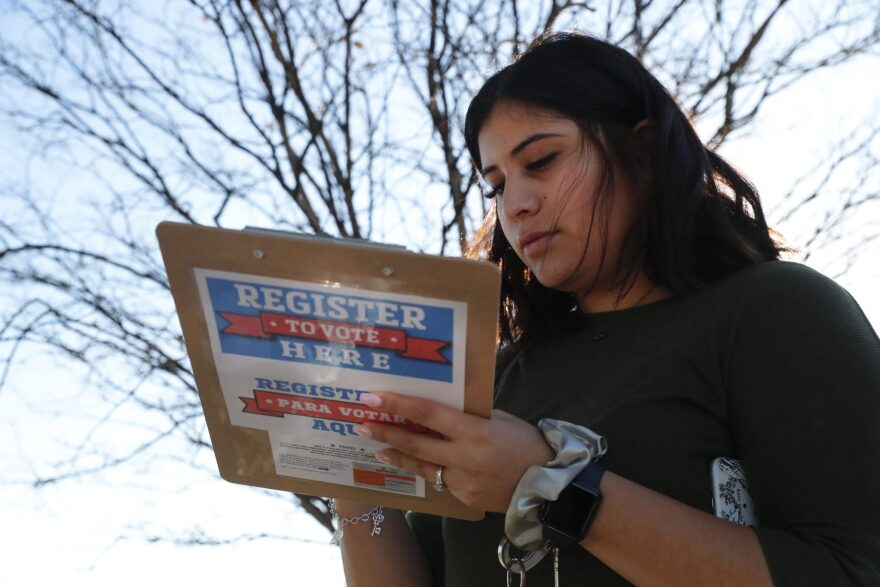 Karina Shumate, a college student studying stenography, fills out a voter registration form in Richardson.