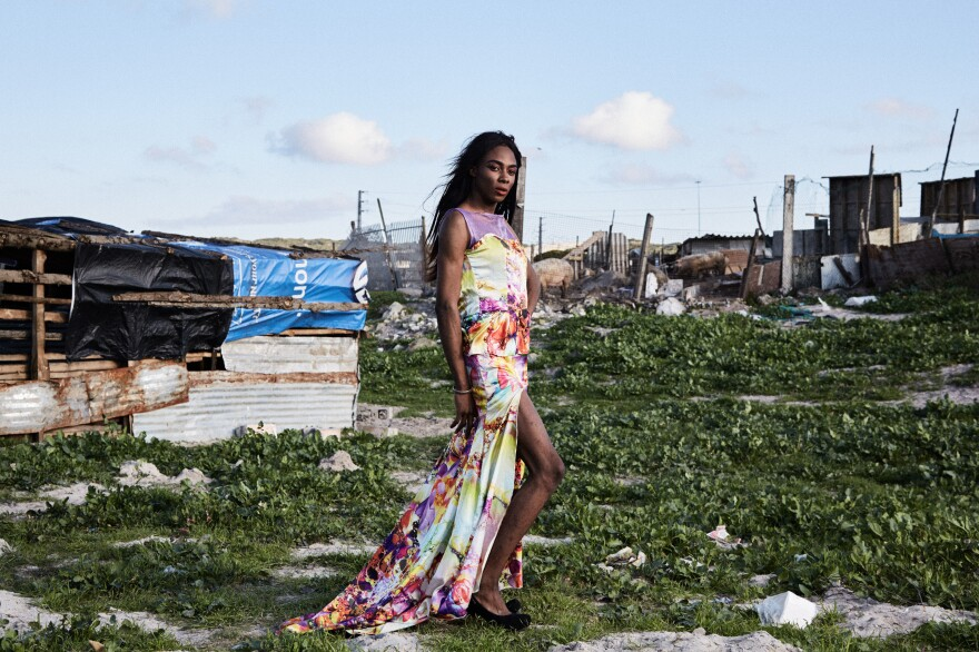 "Shakira Mabika, 24, emigrated to South Africa from Zimbabwe, where the former president ""has referred to people like me as 'pigs' and un-African."" She asked to be photographed by dilapidated shacks where pigs were kept behind a fence. ""I moved to Cape Town in search for a space where I could live my truth,"" she says. But she says she has faced transphobia and still hasn't found a job."