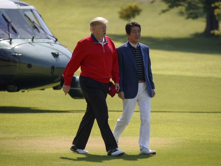 President Trump walks with Japanese Prime Minister Shinzo Abe before playing a round of golf on Sunday in Shiba, Japan.
