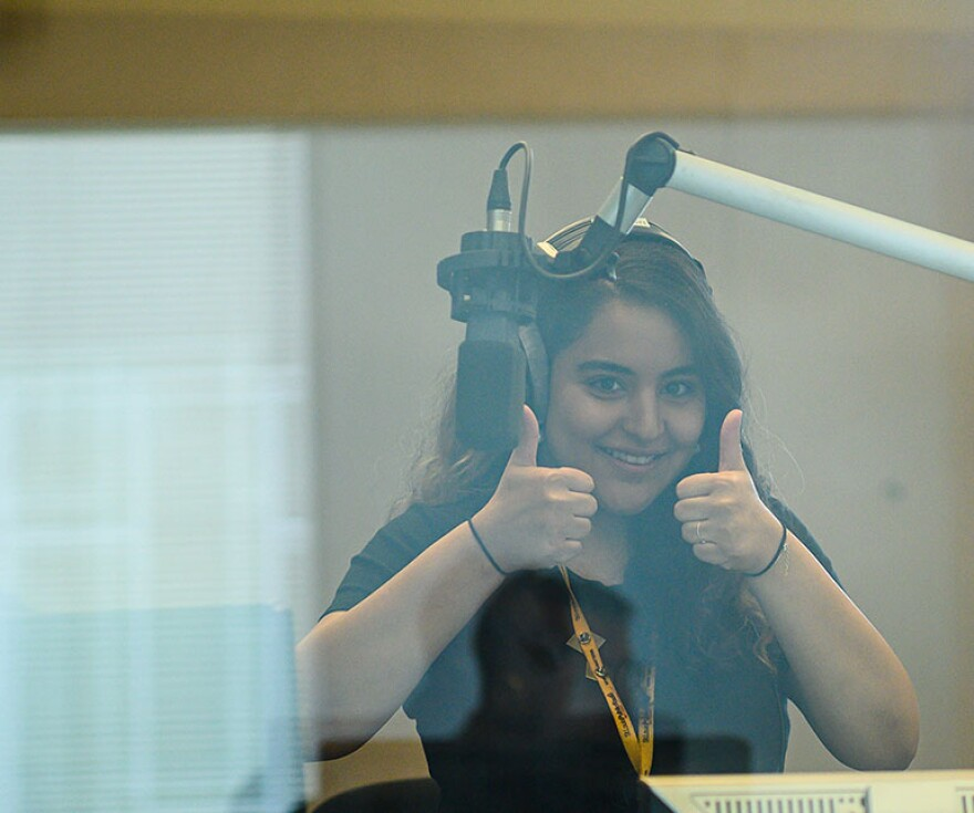 Producer giving thumbs up, behind glass