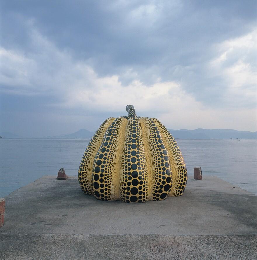 Yayoi Kusama's work <em>Pumpkin  </em>perches at the end of an old concrete pier.<em></em>