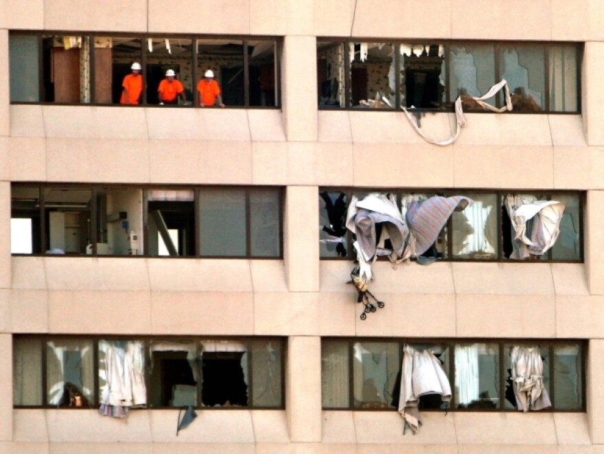 Workers look out from shattered windows on an upper floor of the St. John's Regional Medical Center in Joplin, Mo., in late May, after a tornado severely damaged the hospital.