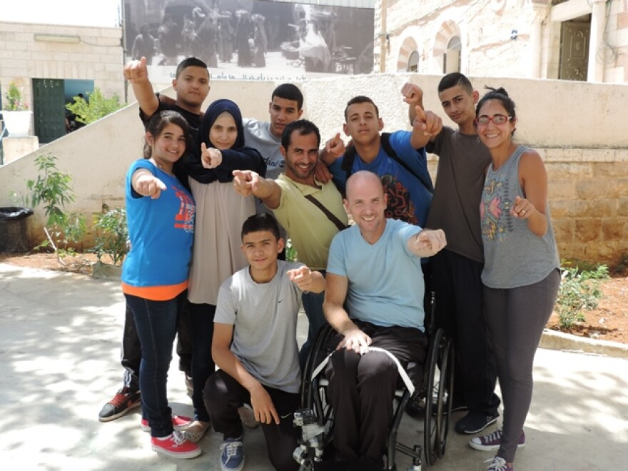 Scheuneman poses with teachers and some of the class' deaf students.deaf students he