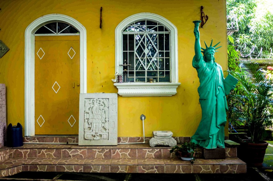 A replica of the Statue of Liberty is displayed on the front porch of a house in Intipucá, El Salvador. Its residents once lived in the United States.