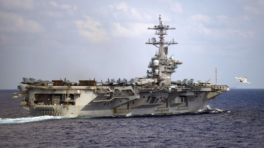 The aircraft carrier USS Theodore Roosevelt is in the western North Pacific Ocean on March 18. The Navy has recommended reinstatement of the ship's captain who was fired after pleading for help with the coronavirus infection onboard.