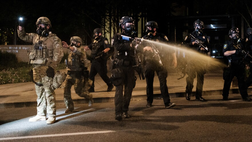 Federal officers use tear gas and other crowd dispersal munitions on protesters outside the Multnomah County Justice Center on Friday in Portland, Ore.