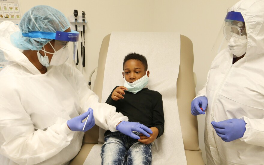 Nurse Nellie Smith (L) holds down the hand of eight year-old Kayden Tree, before inserting a swab into his nose during a COVID-19 test, at a CareSTL Health testing Site, in St. Louis on Monday, May 11, 2020.