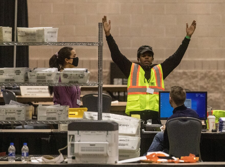 An election worker talks with a colleague during ballot counting Nov. 6 in Philadelphia. Pennsylvania certified its election results on Tuesday.