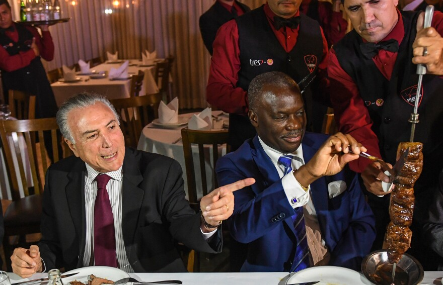 Brazil's President Michel Temer, left, held a dinner at a <em>churrascaria</em> in Brasilia to reassure ambassadors, such as Angola's Nelson Manuel Cosme, that the meat their countries are buying is of high quality.