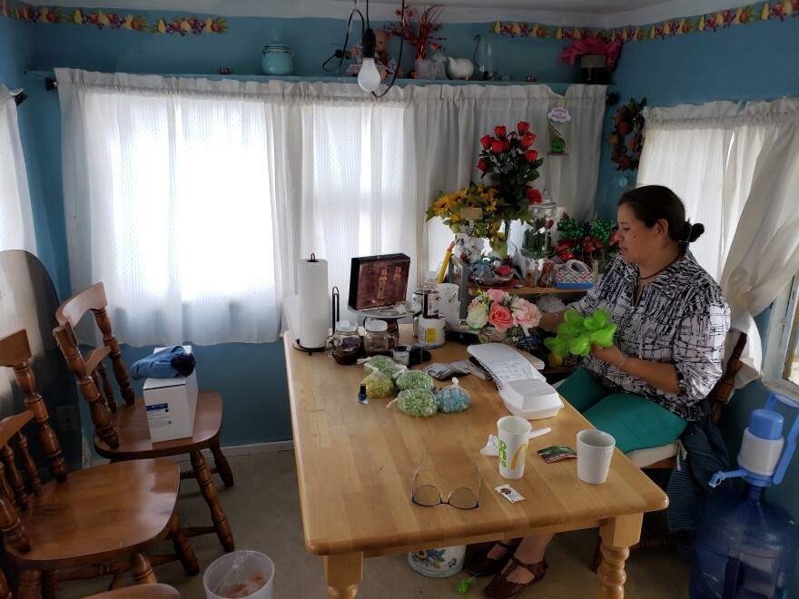 Irma Ibarra sits in her home at Riverside Trailer Court making plastic flower arrangements that she sells on the side.