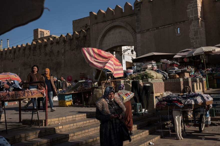An outdoor market selling produce, household items and second-hand clothing is seen outside the entrance to Sfax. Second-hand sellers have become more common in Tunisia as people haven't been earning enough to buy new goods or are selling their own things.