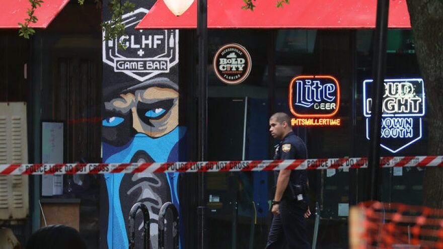 A JSO officer walks by the Chicago Pizza & Sports Grille and GLHF Game Bar.