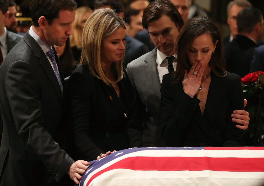 Jenna Bush Hager and her sister Barbara Bush stand with the husbands Henry Chase Hager, left, and Craig Coyne as they pay respect in front of the casket of the late former President George H.W. Bush as he lies in state in the U.S. Capitol Rotunda Tuesday in Washington, D.C.