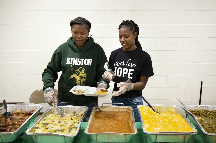 "Lori Carmon, left, whose daughter Michyla Dove plays on the team, and team assistant KJay Johnson, right, serve food during the jamboree games hosted by Kinston High School. Carmon woke up at 1 a.m. to start cooking all of the food. She is a constant fixture at every game and says that, ""I have one child but I've gained many... There's nothing like being a team mom."""