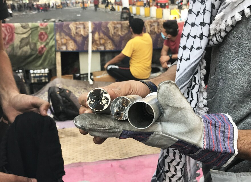 Iraqi protesters hold spent tear gas canisters fired by security forces. Many of the protesters who have been killed were hit in the head by tear gas canisters that were fired directly at them. The protesters wear protective gloves to pick the canisters up and throw them back at security forces.