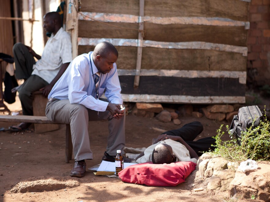 A palliative care physician visits an HIV-positive patient who lost her family to the AIDS epidemic. She's resting on a mat outside her home.