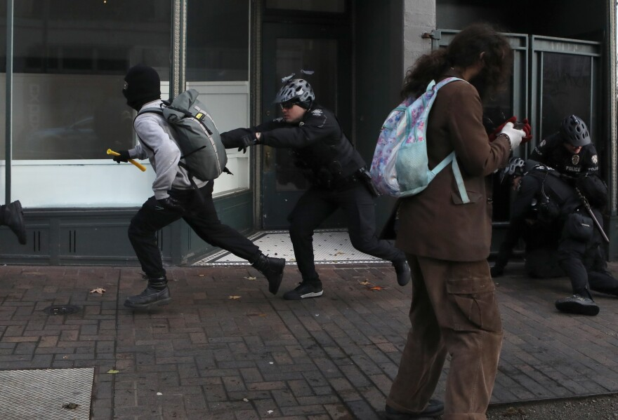 A Seattle police officer chases an anti-fascist protester during the United Against Hate rally by the Washington Three Percent in Seattle last month.