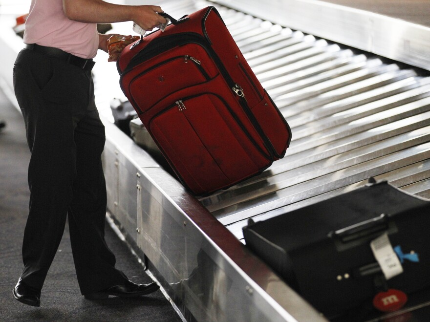 A traveler collects his bag from a luggage carousel in the Philadelphia International Airport in 2011. Baggage fees have helped financially desperate carriers stay aloft.