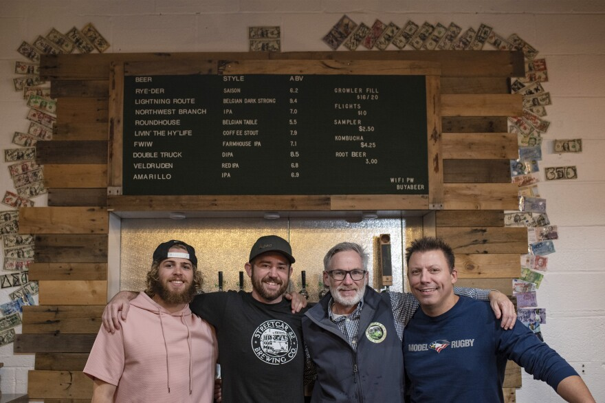 Bartender Zane Pederson (left) and co-founders Jon Cetrano, Mark Burke and Sam Costner stand behind the brewery's bar.