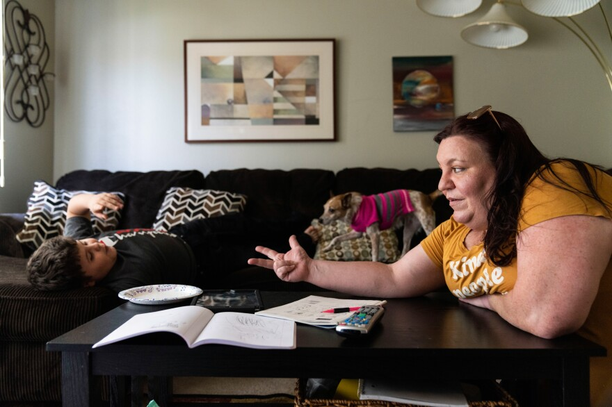 Jessica Barrera helps her son Niko, 10, with math homework after a day of virtual learning at their home in Eau Claire, Wis.