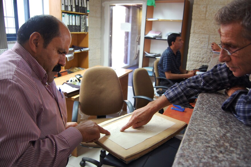 A government clerk in Ramallah helps a Palestinian man look up 1935 property tax records showing his family name. Handwritten ledgers from the times of Ottoman, British and Jordanian rule are still used to help determine Palestinian land ownership.