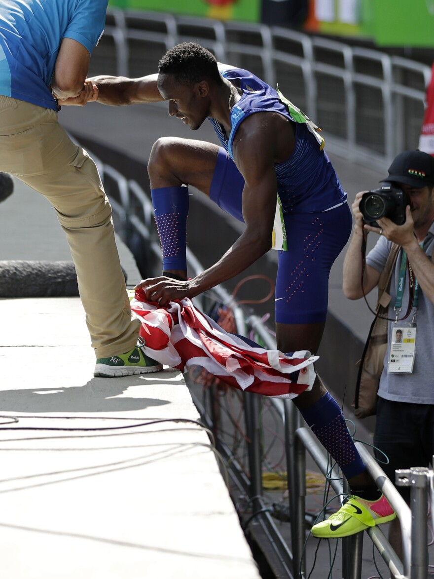 American Will Claye climbs back to the track after proposing to his girlfriend in the stands. He went into the crowd to propose right after he won the silver medal in the triple jump on Tuesday.