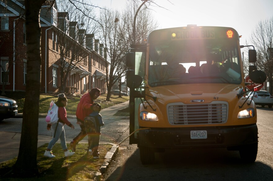 Samuel Williams helps his two children onto the Jefferson Elementary School morning shuttle bus Friday, March 2, 2018. Williams said since it started in January, the shuttle provides safety and a routine for getting to school.