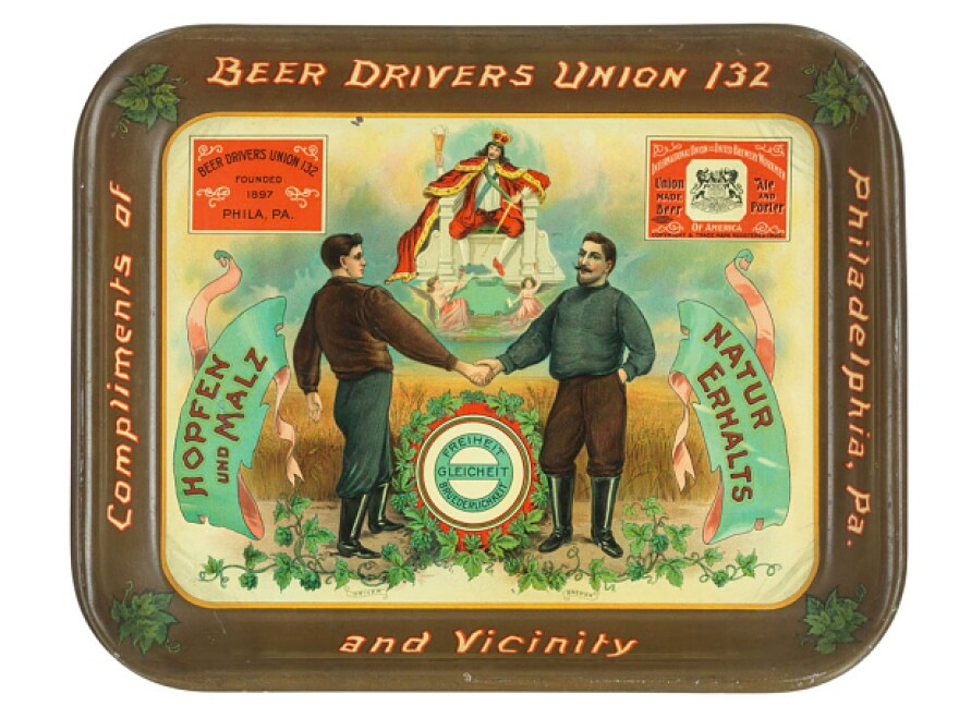"This beer tray, circa 1905 — from the Beer Drivers Union 132 — shows a driver and a brewer working together. It says in German ""Liberty, Equality, Fraternity."""