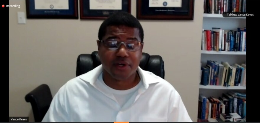 A screenshot of Vance Keyes, wearing a white shit and glasses, speaking during a virtual event. He's in a white-walled room with a bookshelf behind him.