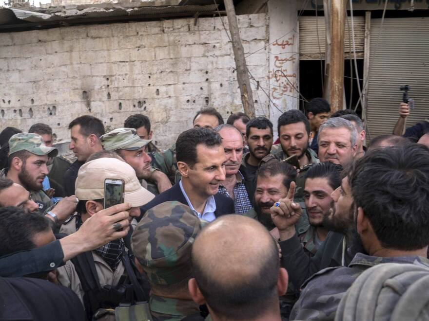 Syrian President Bashar Assad, center, speaks with Syrian troops in newly captured areas of eastern Ghouta, near the capital Damascus, Syria, Sunday. Al-Ikhbariya TV broadcast images of Assad surrounded by soldiers on a street in eastern Ghouta, where a Syrian offensive has been underway over the past month. It was not clear where in eastern Ghouta Assad was.