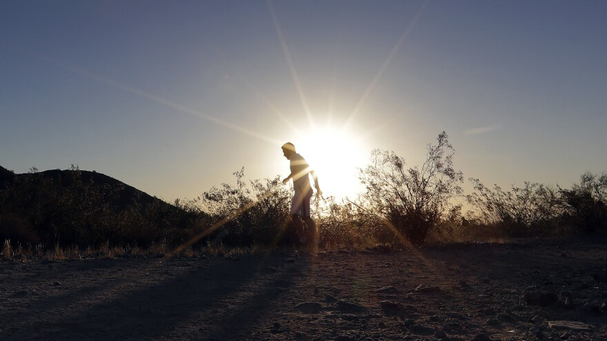 A man runs through section of South Mountain Park at sunrise to avoid the excessive heat in Phoenix.