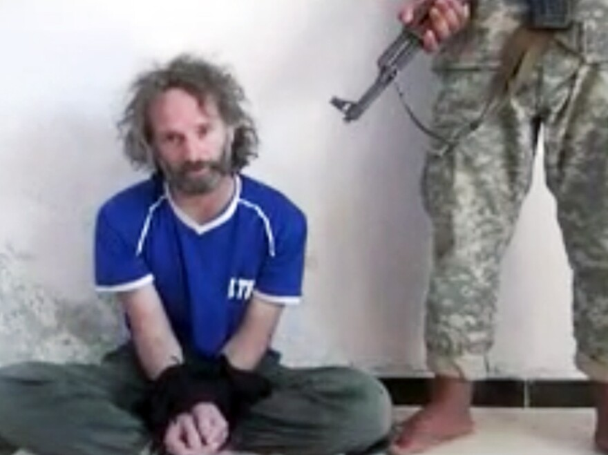 In this image made from undated video obtained by The Associated Press, a man believed to be Peter Theo Curtis, a U.S. citizen held hostage by an al-Qaida linked group in Syria, delivers a statement.