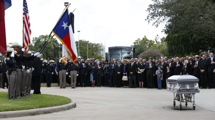 Mourners stand near the casket of Harris County Sheriff's Deputy Darren Goforth at Second Baptist Church in Houston, Texas, on Friday. Two people who were with the deputy on the night he was killed told his family Friday that he wasn't alone when he died.