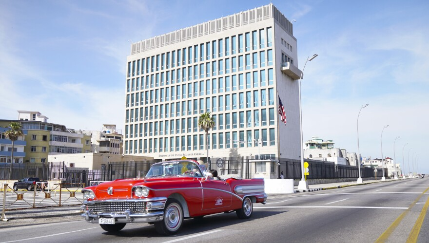 A car drives past the U.S. Embassy in Havana in 2019. Dozens of Americans working at U.S. diplomatic missions in Cuba and China in recent years have suffered from ailments that have included headaches, balance problems and memory loss.