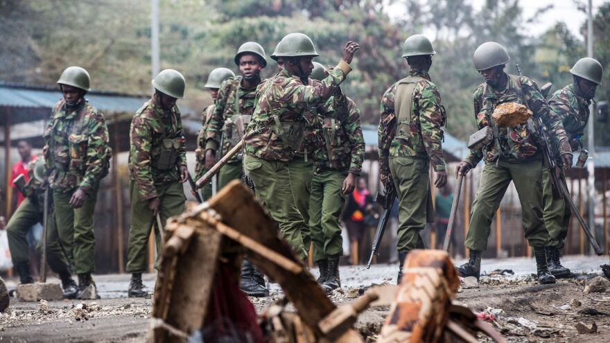 Kenyan police officers clear debris from a barricaded road Friday after an opposition protest roiled a Nairobi neighborhood.