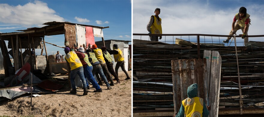 Contract workers hired by the authorities tear down a settlement.