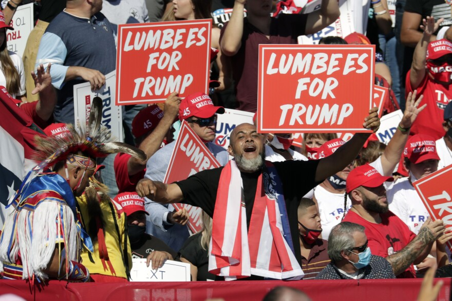 Supporters hold 'Lumbees for Trump' signs as President Donald Trump speaks during a campaign rally at the Robeson County Fairgrounds in Lumberton, N.C., Saturday, Oct. 24, 2020.