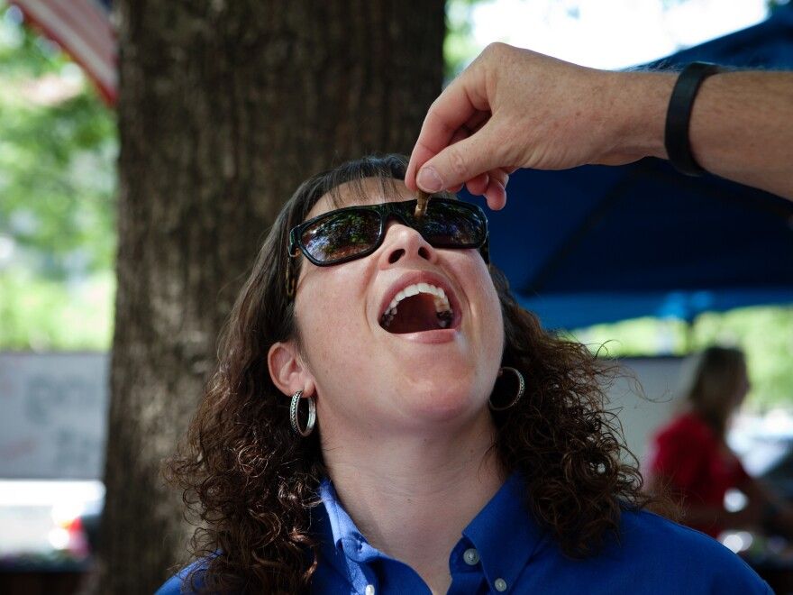 Nancy Troyano, an entomologist with Ehrlich, tries her very first insect.