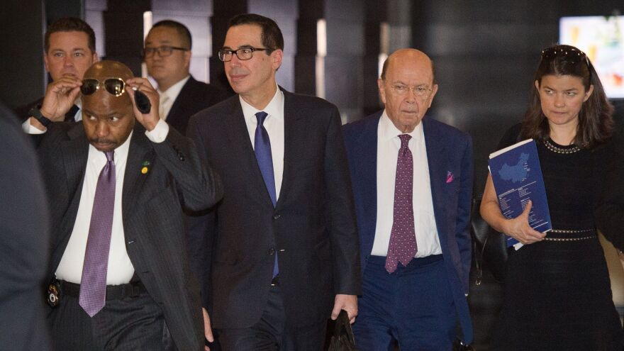 "Treasury Secretary Steven Mnuchin (center left) and Commerce Secretary Wilbur Ross (center right) walk through a hotel lobby as they head to a state guest house to meet Chinese officials in Beijing on Friday. The talks included a ""thorough exchange of views,"" Chinese media report."