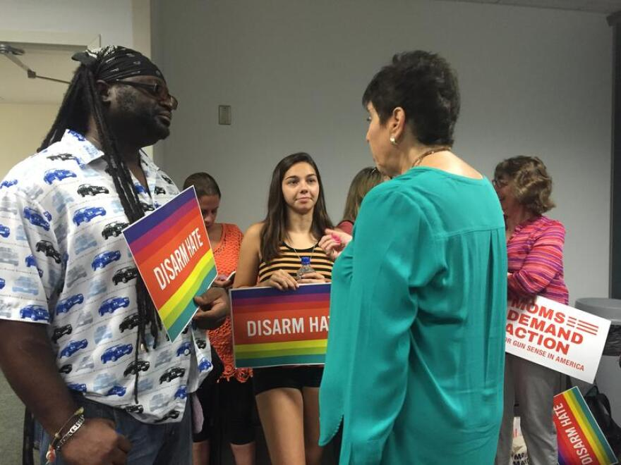"""Members from the activist group """"Moms Dedicated To Action"""" held signs that read """"Disarm Hate"""" at the news conference at the Fort Lauderdale airport Tuesday morning."""