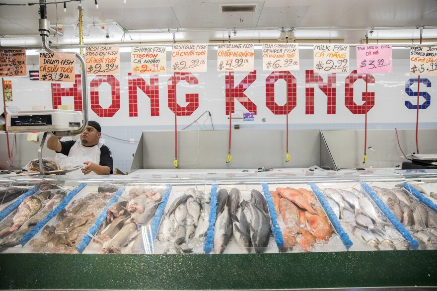 A worker weighs fish at a predominately Vietnamese grocery store.