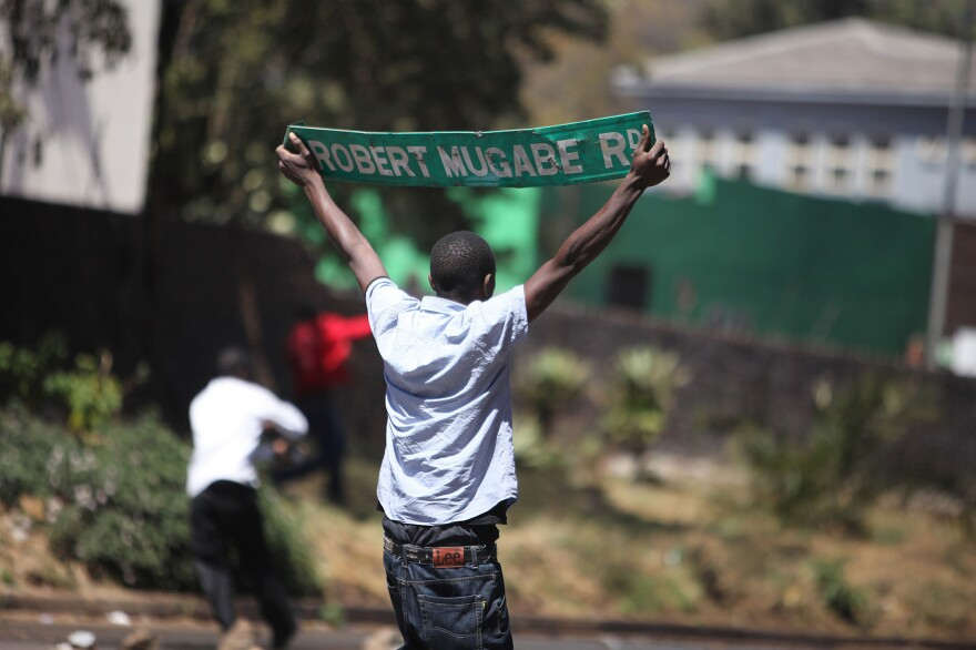 A protester holds up a street sign with President Robert Mugabe name on it as Zimbabwe opposition supporters clash with police during a protest march for electoral reforms on August 26, 2016 in Harare. Riots erupted in Zimbabwe's capital Harare after police fired tear gas and beat protesters who responded by throwing stones in the latest of a string of tense demonstrations.