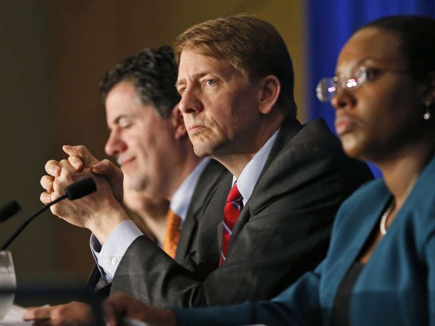 Consumer Financial Protection Bureau Director Richard Cordray (center) listens to comments during a field hearing on payday lending in Richmond, Va., in May.