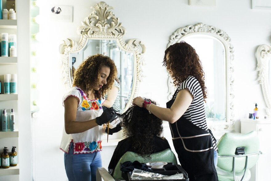 Gerlin Santos (left) and Cristina Gandia (right) dye Lisney Santiago's hair at OM Studio in San Juan.