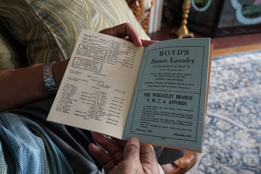 Native St. Louisan John Wright holds open the inside of the 1934 St. Louis Negro Business and Trade Directory.  It was published by the Urban League of St. Louis. The guide offered African American doctors, lawyers, florists, cleaning services and more.